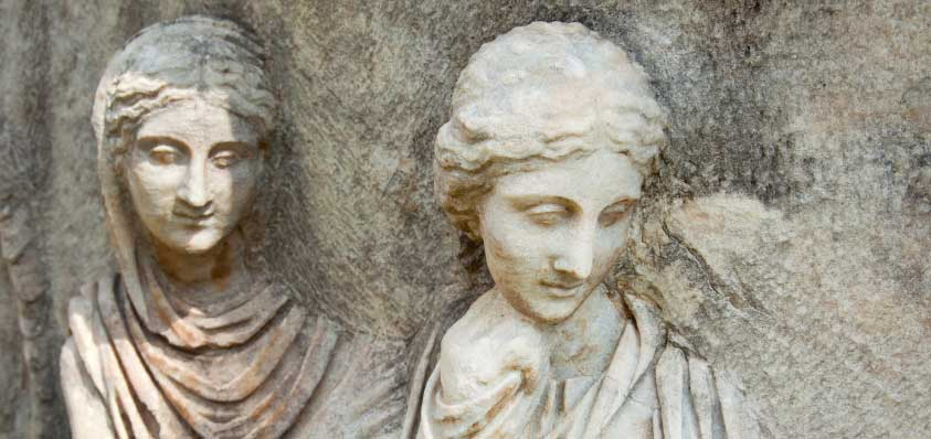Sculpture of a man and a woman on Greek ruin