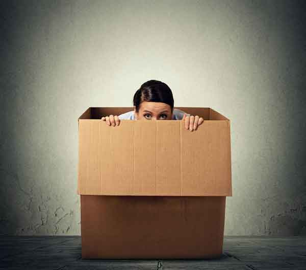 Young lady peeping out of a box