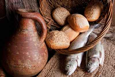 five bread rolls and two fish next to an earthenware jug