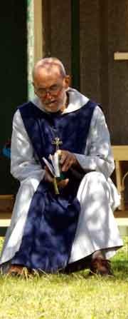 Br John Edwards sitting outside, reading his Bible